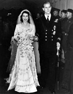 Here comes the bride    Princess Elizabeth wed Philip Mountbatten in 1947 in Westminster Abbey. Designed by Norman Hartnell, the dress was made of ivory satin and embroidered with flowers and thousands of pearls imported from the U.S. The queen famously saved her ration cards in order to buy the material used in the dress. The diamond tiara originally belonged to her grandmother, Queen Mary, and was then handed down to Elizabeth's mother who lent it to her daughter for the wedding.