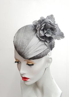 I have blocked a button base in buckram, this is then covered in pale grey silk. The top has handmade matching silk roses and leaves and a pleated silk sash. The hat has millinery elastic for comfort fixing. All handmade by me in the UK and ready to ship