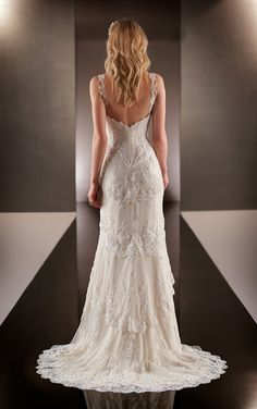 Absolutely exquisite lace gown in a mermaid style. The dress has gorgeous lace applique scallops along the shoulder straps and into the semi-deep v-back. The sweetheart neckline flows into tiered laye