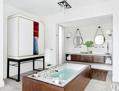 A guest bath is outfitted with BDDW mirrors and a wardrobe by Booth | archdigest.com