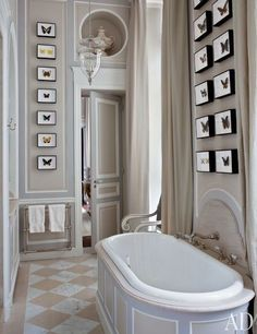 An American couple called on designer Jean-Louis Deniot to channel an 18th-century French aesthetic in their Paris apartment. The narrow master bath's gray-and-taupe paneling is decorated with framed butterfly specimens | archdigest.com
