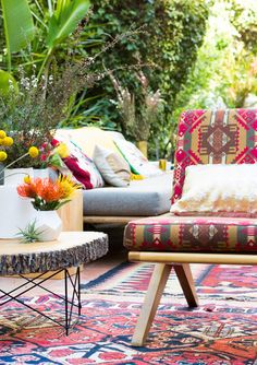 Stunning global styling. Beautiful eclectic prints, stump side table, layered kilim rugs, fresh blooms... Gorgeous!