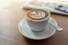 cup of cappuccino coffee art with newspaper