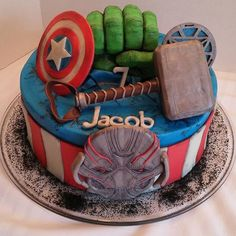Jacob's Avengers, Age of Ultron cake! 12 inch round cake, all buttercream and candy clay details, with candy clay Ultron, Captain America's shield, Iron Man's chest piece, Hulk's fist and Thor's hammer! Hulk's fist and Thor's hammer made with rice krispy treats and candy clay! All edible and no fondant! #cakes #buttercream #nofondant #avengersageofultron #avengers #hulk #ironman #captainamerica #ultron #thor #marvel #candyclay #wiltoncakes #angelascakes Dark Chocolate Candy, White Chocolate Raspberry, Modeling Chocolate, Chocolate Fudge, Ironman Cake, Avenger Cake, Hulk, Superhero Cake, Just Cakes