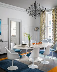 Generally Im' not a fan of all white walls but the gorgeous shot of colour in the Tulip chairs, the rug and pattern curtains bring this space to life.