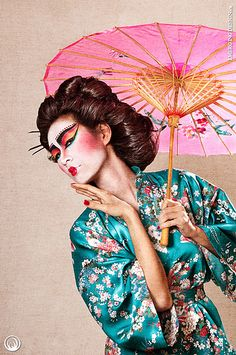 Taking the classic elements of a Geisha, pump it up a notch to make it a high-fashion beauty shot with dramatic make-up, the bright complimentary colors of the turquoise silk robe & the pink umbrella yet the model still holds her hands delicately like the classic Geishas. Well done.
