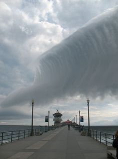 A huge wave-shaped cloud appears to break over California's Huntington Beach Pier~