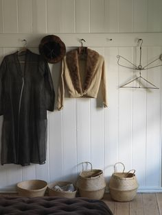 white bead board in mud room with shelving across the top of bead board with hooks for coats.