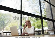 Attractive young female having smart phone conversation while sitting in modern loft interior with big windows and garden view, student of freelancer work on laptop computer or net-book in coffee shop - stock photo
