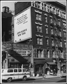 "John Albok (1894-1982)  View of [John Albok's] tailor shop at 1392 Madison Avenue with billboard of ""John Albok's New York"". MCNY Collections Portal"