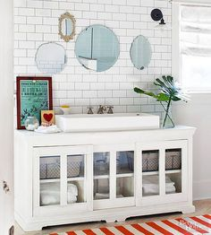 A long media cabinet becomes the perfect base for a trough sink while providing plenty of additional counter space. Glass-front sliding doors on this DIY bathroom vanity make for grab-and-go storage with style./