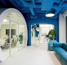 Vibrantly Colored Media AgencyOffice Design in Moscow - This image shows the receiving area of your main office. Of course, since the theme is mainly white and blue, a blue comfy sofa would work.