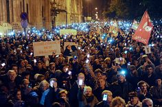 Hungarian citizens lift their mobile phones to protest against the goverment's new tax plan for the introduction of the internet tax next year in Budapest downtown on October 26, 2014. (AFP Photo/Attila Kisbenedek)