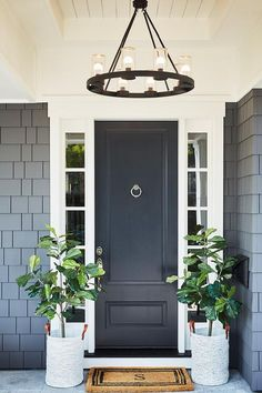 A monogrammed door mat flanked by potted fiddle leaf fig plants is placed in front of a black front door flanked by white sidelights lit by a ring chandelier. Black Exterior Doors, Front Porch Decorating, Craftsman Front Doors, Front Door Lighting, Exterior Entryway Ideas, Transitional House, Front Entry Doors, Front Door Styles, House Exterior