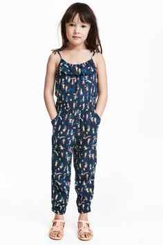 Patterned jumpsuit: Jumpsuit in a soft, patterned viscose weave with narrow shoulder straps with a sewn-on bow and elastication and a frill at the top. Elasticated seam at the waist, side pockets and long legs with elasticated hems.