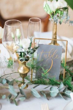 Rather than completely imitating the era, this reception table intertwines its elements into a subtle, contemporary style. Brass candlesticks, simple and elegant table numbers in a gilded frame, and foliage nestle together for a beautiful centerpiece. Centerpiece by stylist Daisy Says I Do.