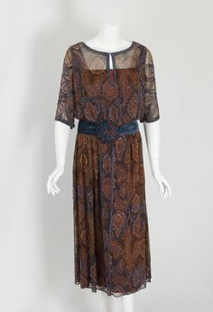 Beaded chiffon dress, early 1920s. This treasure of textile art was made from silk chiffon printed with Persian-style motifs. The rich muted shades of brown, gold, turquoise, blue, and rust are accented with blue-and-rose glass beads to stunning effect. The dress is constructed in layers attached at the waist to an inner petersham. The slip layer under the chiffon is of brown taffeta with an upper yoke of matching tulle. The under bodice is of ivory charmeuse.