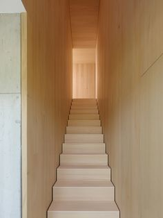 Wooden staircase inside the s_DenK house by SoHo Architektur.