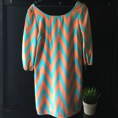 """Blueish green and corral chevron dress A beautiful chevron dress. Zipper from top to bottom on the back of the dress. 3/4"""" sleeves. Looks stunning!! 100%polyester. By together Dresses Midi"""