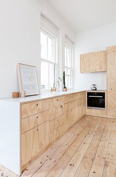 A modern kitchen with unstained plywood floors and cabinets.