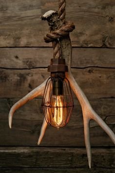 This is the Caged Stag Pendant light. The electrical cord has been hand wrapped inside of 3/4 Manila rope and then looped and securely attached to a Grade A Antler Shed. The antler has been Organically shed. Ive used a rustic cage and pipe fitting socket cover to give it a little more of an industrial look. I love the blend of nature/industrial. This light is a great for swag hanging in a corner, or hardwiring as a center piece over your dinning table!  These lights come with a Standard Plug…