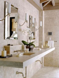 spa vanity.  a thick slab countertop of travertine stretches across this master bath defining the double vanity.  the walls and floor are tiled in the same stone to create a calm, unified space.  modern wall-mount nickel faucets add an artistic element, and mirror-framed mirrors give the space a hint of sophistication and contrast.