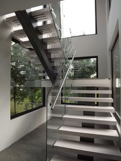 Solid wood staircase on powder coated beam with tempered glass railing and stainless steel handrail