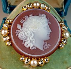 A Victorian Era Antique Cameo Brooch Pin. French, circa 1870, a finely carved carnelian cameo of Dionysus, the Greco Roman god of wine making and fertility,  set in 18K gold bezel embellished with half pearls and rose cut diamonds, width 37 mm (almost 1 1/2 in.), Marked with French eagle-shaped assay mark, The cameo brooch comes in its original blue velvet retailer's case stamped in gold.  165 PALAIS  ROYAL NATIVELLE PARIS