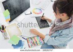 High angle view of an artist drawing something on graphic tablet at the office - stock photo