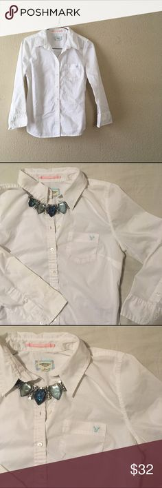 """American Eagle White Dress Shirt Simple, casual collared dress shirt/GENTLY USED AND IN very nice CONDITION/buttons at cuffs/small pocket on breast with embroidered AEO eagle. This is great to wear under cardigans for a more work casual look! Super cute! Measurements: armpit to armpit length @ 18""""//total length @ 22"""" American Eagle Outfitters Tops Button Down Shirts"""