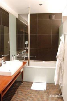 Glo**** - De ruime badkamer met bad/douche combinatie.