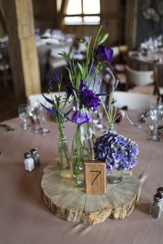 wild flower centerpiece in random vases on wood slabs, I already have the tree trunk slabs and vases. we could even add candles in little mason jars which i also already have...