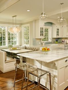 traditional kitchen with built in banquette dining table seating and ghost acrylic bar stools marble island