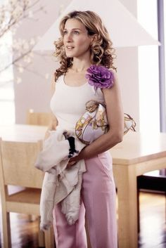 Carrie Bradshaw wears a tank tucked into pink trousers, and accessorizes with a flower brooch and a scarf print bag