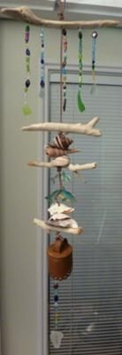 Sea Glass Mobile Chimes Driftwood and shells are drilled. Sea Glass and beads are strung on fishing line.   Telephone line is then string through all items and tied in a loop