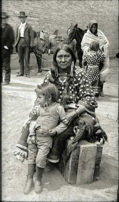 """Title ~ """"Medicine Crow"""", ca. 1900. Sheridan, Wyoming. Photo by Louis R. Bostwick. ~ Medicine Crow and son, pose photographed outdoors resting on a wooden crate. Medicine Crow wears a fringed dress decorated with elk teeth, and beaded earrings. Men with horses and a mother and daughter are seen nearby."""