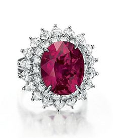 Lot 140 - A RUBY AND DIAMOND RING, BY CARTIER Designed as a graduated double row of rectangular-cut emeralds, extending a pear and circular-cut diamond fringe, joined by circular and pear-shaped diamond clusters to the circular-cut diamond double row backchain, mounted in platinum, 1955, 14 ins. With maker's mark for Harry Winston