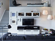 A living room with a black-brown TV bench with white drawers and wall cabinets with white doors and tempered glass panels.