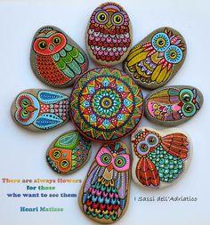 Motifs de chouettes peintent sur des galets et positionnées en forme de fleur