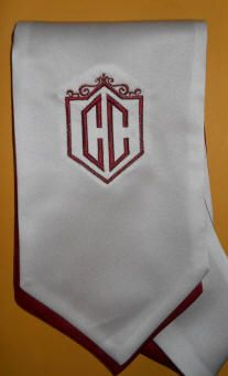 Shield monogram on stole in gold and white.