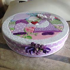 Tampa da caixa redonda lilás, em tecido, usando técnica de patchwork embutido.