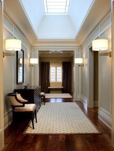 Reflecting the home's exterior details, this long upper hall has a rhythmic pattern of doorways, arches and sconces. To achieve symmetry, the three windows were draped to look like two. This clean, open, contemporary interior responds to this young family's modern tastes, but references the home's traditional exterior elements, grey-brown stone / black-brown trim, in elements such as the flooring material and stair's dark steel patina. Douglas Design Studio