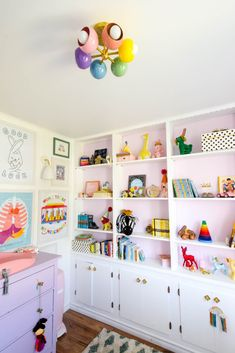 White built in bookcases with wood floors and rainbow accent pieces. Built In Bookcase, Bookcases, Baby Girl Nursery Decor, Baby Room, Flush Mount Kitchen Lighting, Gender Neutral, Accent Pieces, Colorful Interiors, Modern Interior