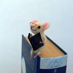 Felt miniature white mouse bookmark reading a book. His long tail is trapped in the book, but does not care because is reading very interesting book. His book is made of real paper. Wonderful present for someone who is keen on reading books. This funny miniature animal is cute, comical and whimsical. The miniature mouse is made out of wool and is needle felted.  Great present for everyone who admires handmade Eco-friendly creations. Felt miniature white mouse is about 2,5 inches or 6,5 cm…