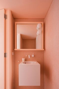 Эта современная половина ванны покрыта крошечными персиковых плитки, которые соответствуют персиковый потолок, и создает монохромный внешний вид