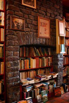 A bookshop converts a fireplace into a bookshelf to accommodate more books.