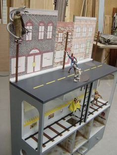"""""""Action Figure City"""" is a kind of doll house with a multilayered city scene painted on. Made in the USA."""
