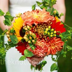 Laura's bouquet was made up of her favorite fall flowers: Sunflowers, gerberas, orange dahlias, hypericum berries, and bupleurum. Inside the bouquet was a special charm with a picture of Laura's mother, which was a gift from her sister.