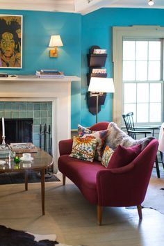 Bohemian Eclectic Scandinavian Furniture: A fuchsia settee nearby a glass-tiled fireplace .