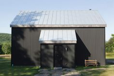 The exterior of the barn is clad in black corrugated aluminum SIPs. The standing seam aluminum roof is typical of the vernacular architecture in this part of New York. There are no windows on the front facade to keep insulation factors at their highest. Design Exterior, Rustic Exterior, Black Exterior, Modern Exterior, Exterior Paint, Bungalow Exterior, Stucco Exterior, Exterior Shutters, Craftsman Exterior
